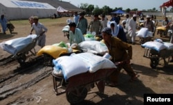 FILE - People fleeing from the military offensive against Pakistani militants in North Waziristan walk away with wheelbarrows of relief handouts from the World Food Program at a distribution point for internally displaced persons in Bannu, located in Pakistan's Khyber-Pakhtunkhwa province, July 6, 2014.