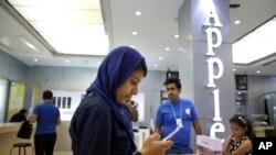 یک زن در حال امتحان کردن یک آیفون در یک فروشگاه لوازم الکترونیک در تهران.