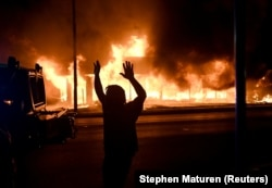 A man walks by an armoured vehicle as B&L Office Furniture burns in the background as protests turn to fires after a Black man, identified as Jacob Blake, was shot several times by police last night in Kenosha, Wisconsin, U.S. August 24, 2020.