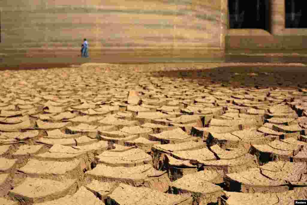Seorang pekerja dari SABESP, sebuah perusahaan Brasil di negara bagian Sao Paulo yang menyediakan layanan air dan pembuangan limbah bagi kawasan perumahan, niaga dan industri, berjalan melalui dam Jaguary yang kering sebagai akibat dari musim kemarau panjang yang melanda negara bagian Braganca Paulista, 100 km dari Sao Paulo. Hawa panas ditambah kemarau panjang telah meniumbulkan kekhawatiran akan kelangkaan air, kegagalan panen dan tagihan listrik yang melambung yang bisa menjatuhkan perekonomian dalam tahun pemilihan Presiden Dilma Rousseff.