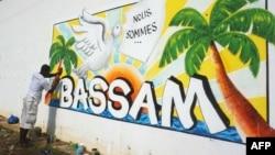Un homme peint un mur dans le cadre du Festival international du dessin animé et de la bande dessinée d'Abidjan de Coco Bulles, en hommage aux victimes de l'attaque de 2016 à Grand-Bassam, le 18 mars 2017.