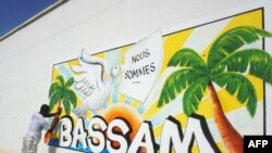 Un homme peint un mur dans le cadre du Festival international du dessin animé et de la bande dessinée d'Abidjan de Coco Bulles, en hommage aux victimes de l'attaque de Grand Bassam 2016 à Grand-Bassam, près d'Abidjan, le 18 mars 2017.