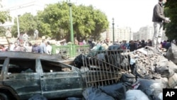 A burned vehicle, piles of rubble and trash in Tahrir Square, Cairo, Egypt, February 12, 2011