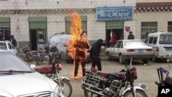 Ảnh một người Tây Tạng tự thiêu. Thông báo treo giải thưởng của Trung Quốc chỉ trích tự thiêu rằng 'một hành vi cực đoan chống lại loài người, chống lại xã hội'