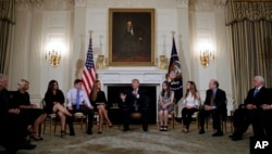 President Donald Trump hosts a listening session with high school students, teachers and parents in the State Dining Room of the White House in Washington, Wednesday, Feb. 21, 2018. (AP Photo/Carolyn Kaster)