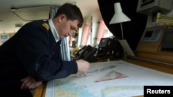FILE - A Russian seaman works on charts aboard the atomic icebreaker Yamal, docked in Murmansk.