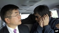 In this photo released by the US Embassy Beijing Press Office, blind lawyer Chen Guangcheng makes a phone call as he is accompanied by U.S. Ambassador to China Gary Locke in a car on the way to a hospital in Beijing, May 2, 2012.