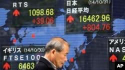 Papan saham elektronik dari perusahaan sekuritas di Tokyo (31/10). (AP/Eugene Hoshiko)