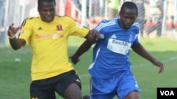 FILE: A Dynamos player fights for the ball with a Chicken Inn defender.