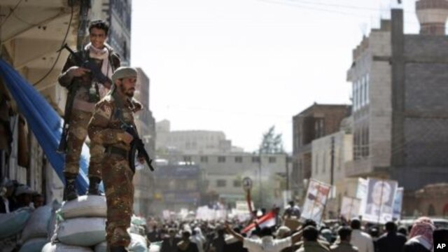 Two Yemeni army soldiers who defected stand guard as protesters march during a demonstration demanding the prosecution of Yemen's President Ali Abdullah Saleh in Sanaa, Yemen, December 1, 2011.