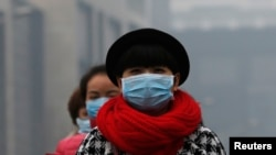 FILE - Women wearing masks make their way amid the heavy haze in Beijing, Feb. 23, 2014.