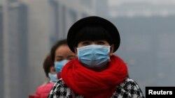 一名女子在北京的雾霾中戴着口罩行走。(资料照片)