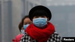 Phụ nữ ở Bắc Kinh mang khẩu trang để tránh không khí ô nhiễm 23/2/14