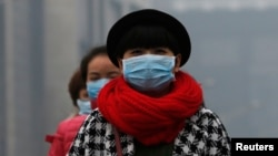 FILE - Women wearing masks make their way amid the heavy haze in Beijing.