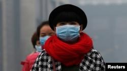 2014年2月23日戴着口罩在北京雾霾中行走的女子