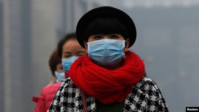 FILE - Women wearing masks make their way amid the heavy haze in Beijing.