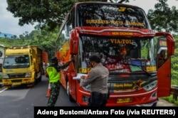Para petugas memeriksa sebuah bus penumpang pada hari pertama penerapan larangan mudik nasional untuk mencegah penyebaran pandemi COVID-19, di Tasikmalaya, Jawa Barat, 6 Mei 2021. (Foto: Adeng Bustomi/ Antara Foto via Reuters)