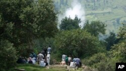Smoke rises behind from a mortar shell fired by Pakistani troops as Indian villagers sit during the funeral of Indian civilian Sarpanch Karamat Hussain who was killed in Pakistani shelling at Balakot sector in Poonch, Jammu and Kashmir, India, Aug.16, 201