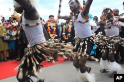 Chinese President Xi Jinping, centre, and Zimbabwean President Robert Mugabe, centre right, watch a performance by Zimbabwean traditional dancers upon his arrival in Harare, Zimbabwe.