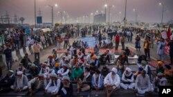 Para petani mendengarkan pembicara di tengah jalan tol di lokasi protes terhadap undang-undang pertanian baru di perbatasan negara bagian Delhi-Uttar Pradesh, India, Sabtu, 5 Desember 2020. (Foto: dok).