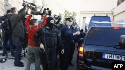 Greek police special forces secure the area as a police van with suspected members of the group Revolutionary Nuclei of Fire, background, enter the court set up inside a maximum security prison in Athens, Monday, Jan. 17, 2011. Nine suspected members of a