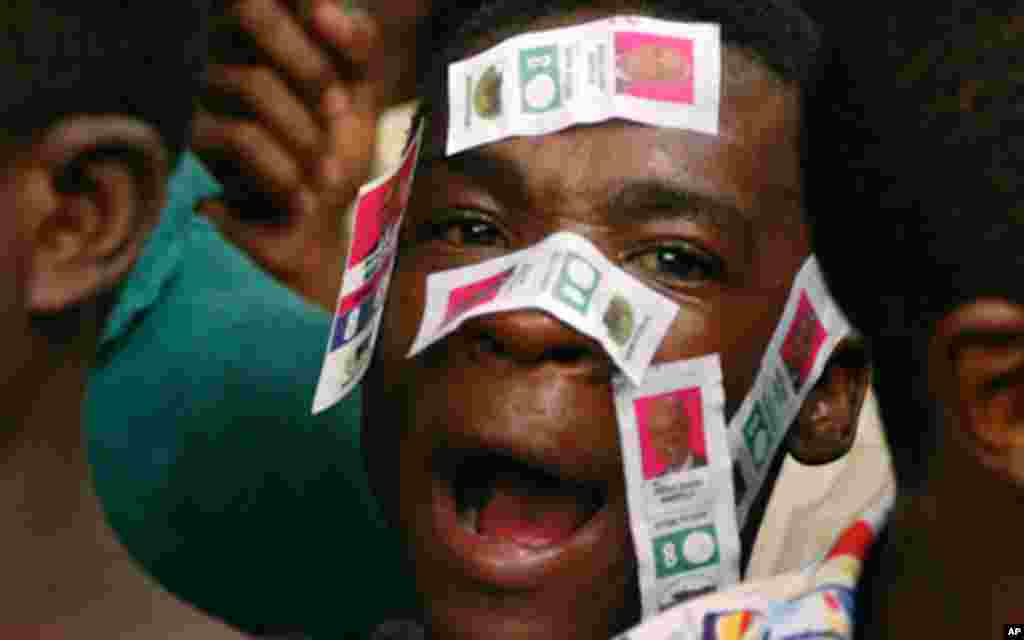 A supporter of Haiti's presidential candidate Michel Martelly, with Martelly's electoral stickers on his face, waits to meet the candidate outside his home in Peguy Ville December 9, 2010. Haiti's electoral authorities said on Thursday they would urgently