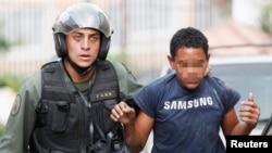 Un menor (al que le hemos tapado el rostro) es detenido por un guardia nacional, luego de las manifestaciones del sábado en Caracas.