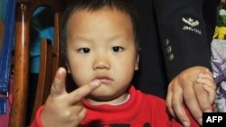 FILE - A young Chinese boy poses as he and a group of children that were recently rescued from child traffickers. Police in China have broken a child trafficking ring that they say had been selling children from the remote southwest to buyers near the coast for as little as about $3,000.