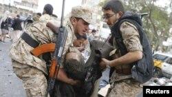 Une victime de l'attentat suicide portée par les agents de la sécurité après l'explosion d'une bombe à Sanaa, Yémen, jeudi le 9 octobre 2014.