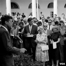 Presiden John F. Kennedy (kiri) memberi ucapan selamat jalan kepada rombongan sukarelawan Peace Corps pertama di Gedung Putih, 28 Agustus 1961.