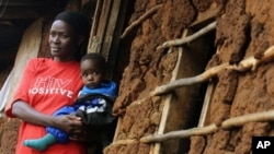 A Kenyan AIDS victim holds her child outside her mud shack in Kibera, Kenya's largest slum, 19 Jul 2005 (file photo)