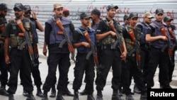Cảnh sát Pakistan canh gác tại tang lễ của các ủng hộ viên đảng Nhân dân Pakistan (PPP), thiệt mạng trong một vụ nổ súng ở Karachi ngày 24/4/2013.Trong thời gian trước ngày bầu cử, phe Taliban ở Pakistan đã tấn công một số đảng chính trị mà họ xem là có chủ trương thế tục.