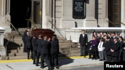 Mimi O'Donnell, former partner of actor Phillip Seymour Hoffman, holds their daughter Willa (in purple) next to their son Cooper as the casket arrives for Hoffman's funeral in the Manhattan borough of New York, Feb. 7, 2014.