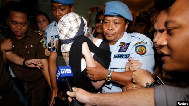 Convicted Australian drug trafficker Schapelle Corby is escorted by police from the prosecutor's office in Denpasar, on the resort island of Bali, Feb. 10, 2014.