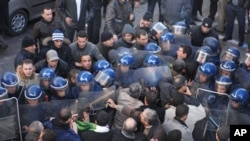 Demonstrators, foreground, asking for political change in their country, face riot policemen, in Algiers, Algeria, 22 Jan 2011