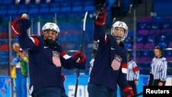 Megan Bozek (izquierda) y Kacey Bellamy celebran el triunfo en la semifinal de hockey para mujeres en Sochi 2014.