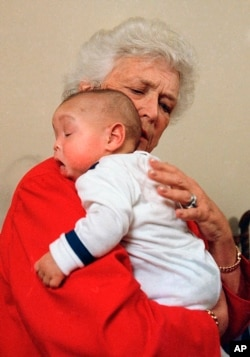 FILE - In this March 22, 1989, file photo, former first lady Barbara Bush holds an infant identified as Donovan during a visit to Grandma's House in Washington. Grandma's House provided residential care for abandoned infants and young children living with HIV/AIDS.