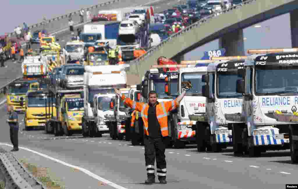 A rescue worker gestures in front of recovery trucks lined up to collect over 100 vehicles involved in multiple collisions, which took place in dense fog during the morning rush hour, on the Sheppey Bridge in Kent, east of London. Eight people were seriously injured and dozens hurt in the multiple crashes.
