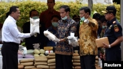 FILE - Indonesian President Joko Widodo (C) and other officials prepare to destroy illegal narcotics during an event in Jakarta, Indonesia, Dec. 6, 2016.