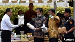 FILE - FILE - Indonesian President Joko Widodo (C) and other officials prepare to destroy illegal narcotics during an event in Jakarta, Indonesia, Dec. 6, 2016.