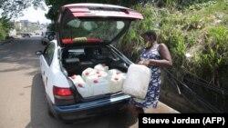 Une femme charge dans un taxi des conteneurs remplis d'eau recueillie dans une source naturelle à Libreville, au Gabon, le 2 février 2021.