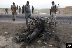 FILE - Afghan security forces gather at the site of Monday's suicide attack near the Bagram Air Base, north of Kabul, Afghanistan, April 9, 2019.