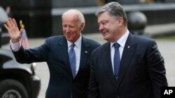 ປ. ຢູເຄຣນ ທ່ານ Petro Poroshenko, ຂວາ, ຍິ້ມ ກັບຮອງ ປ. ສະຫະລັດ ທ່ານ Joe Biden ຍົກມືໃຫ້ບັນດານັກຂ່າວ ທີ່ນະຄອນ Kyiv, ຢູເຄຣນ, 7 ທັນວາ, 2015.