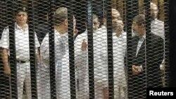 穆爾西(右)與穆斯林兄弟會的其他高級成員在開羅的庭審中