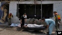 Nhân viên cứu hộ khiêng thi thể nạn nhân ra khỏi hiện trường vụ nổ bom ở Peshawar, ngày 11/5/2014.