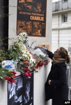 Phụ nữ đặt hoa gần trụ sở của báo 'Charlie Hebdo' sau vụ tấn công chết người.