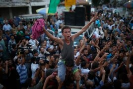 Palestinians celebrate following announcement of a cease-fire in Gaza City Aug. 26, 2014.