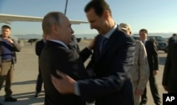 FILE - In a frame grab made available by Russian Presidential TV Syrian President Bashar al-Assad, right, greets Russian President Vladimir Putin upon his arrival to the Hemeimeem air base in Syria, Dec. 11, 2017.