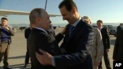 Rusiya prezidenti Vladimir Putin Suriya prezidenti Bəşar Əsədlə Suriyanın Hmeimim hərbi hava bazasında görüşür, 11 dekabr 2017.