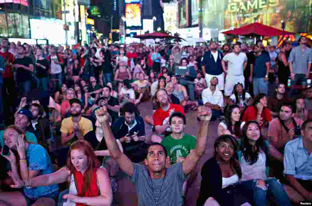 Xavier Cabrera (front, C) of New York, celebrates while watching a live broadcast of the NASA Mission Control center in Time Square, in New York, August 6, 2012.
